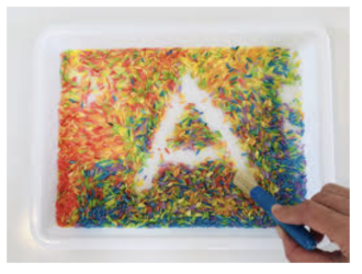 writing letters and words in colored grains of rice